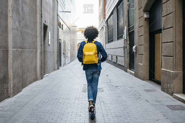 Back view of young man with yellow backpack on E-Scooter in the city- Barcelona- Spain