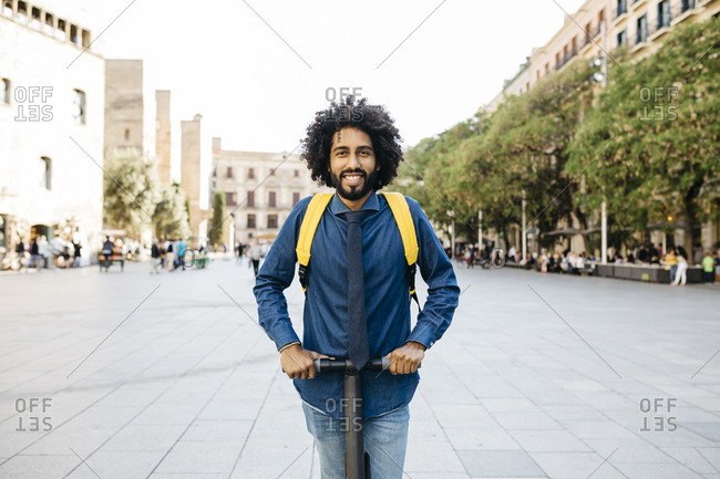 Portrait of smiling man with backpack on his E-Scooter after work- Barcelona- Spain
