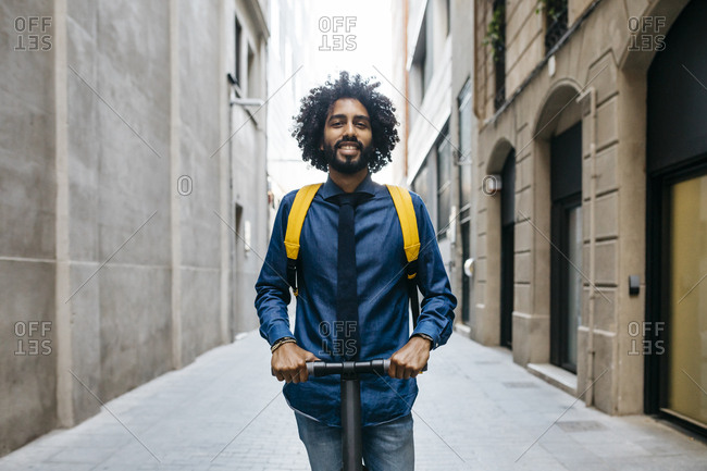 Portrait of smiling young man with backpack on E-Scooter after work- Barcelona- Spain