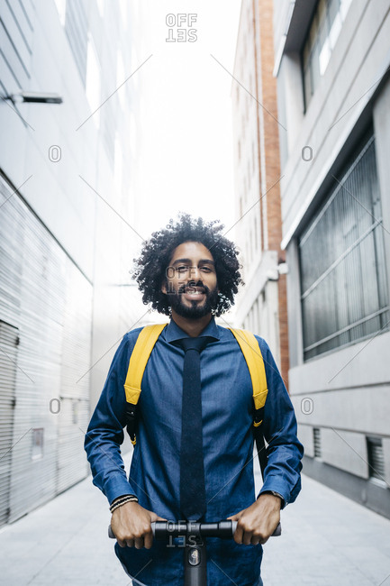 Portrait of smiling  young man with backpack on E-Scooter after work