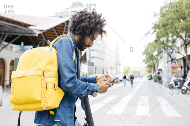 Man with backpack and E-Scooter using navigation app on his mobile phone in the city- Barcelona- Spain