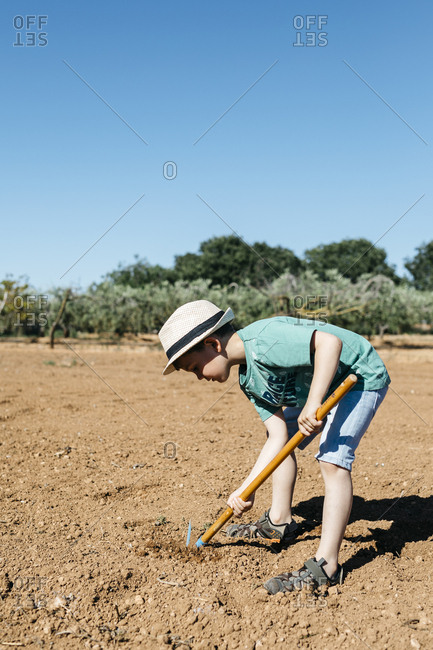 Young gardener plowing the ground