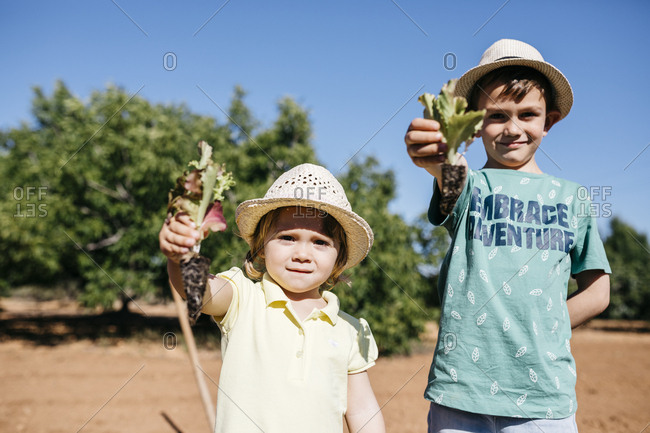 Brother and sister showing the vegetables they are going to plant