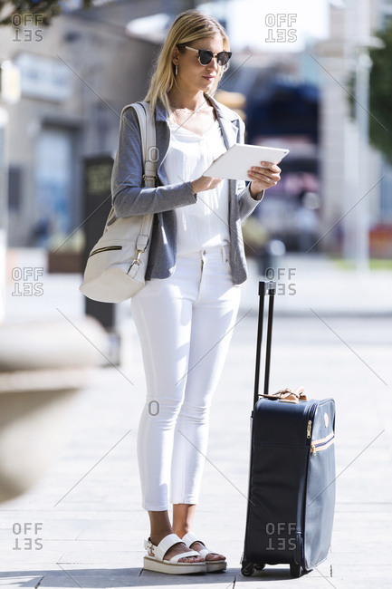 Young businesswoman working with digital tablet while standing with suitcase in the street