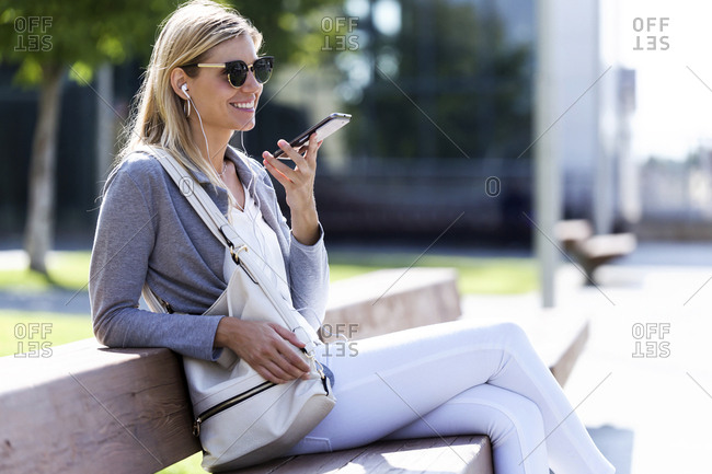 Young businesswoman talking on the smartphone with hands free while sitting on bank