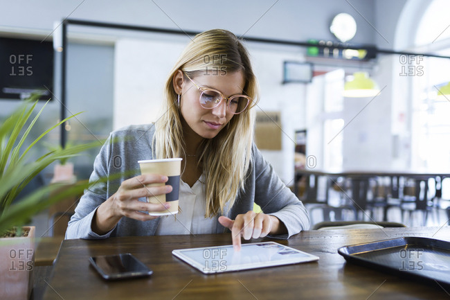 Young woman working with her digital tablet while drinking coffee in the coffee shop