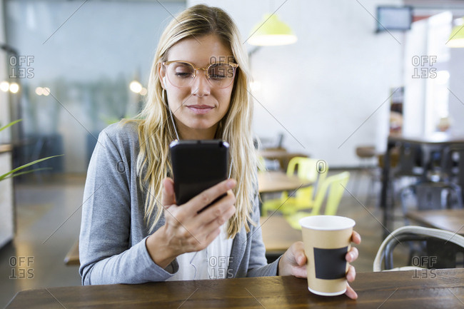 Young woman texting with her mobile phone while drinking coffee in the coffee shop