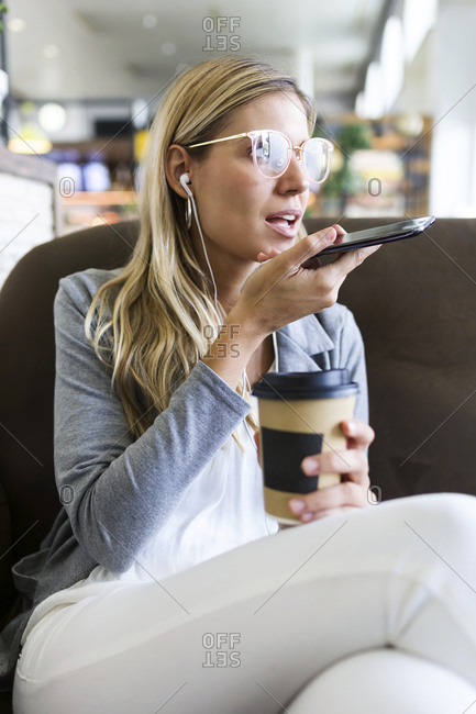 Young woman talking on mobile phone with hands free while drinking a coffee in a coffee shop