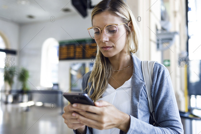 Young woman texting with her mobile phone in the train station hall