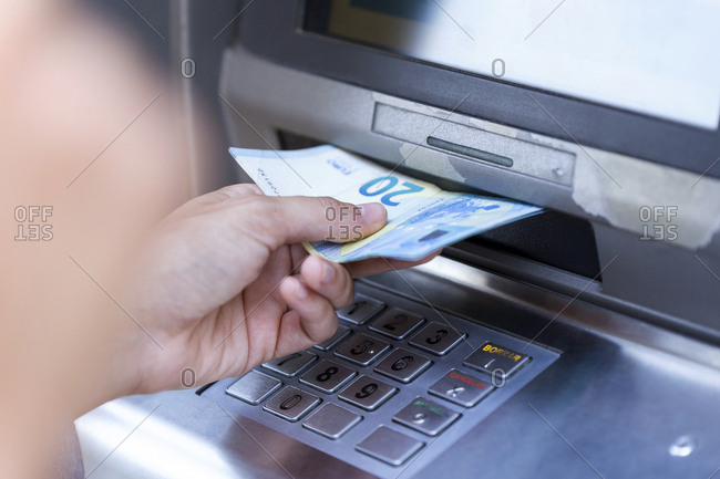 Close up of businesswoman withdraw money on a cash machine