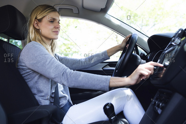 Young woman driver choosing a radio channel in her car
