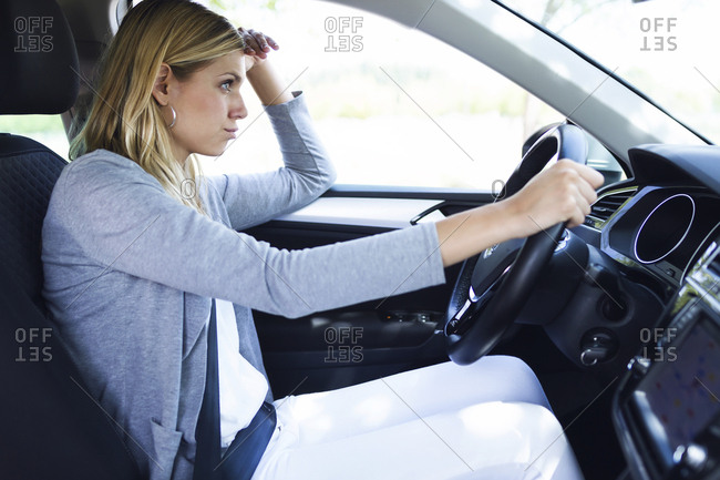 Stressed young business woman driving her car