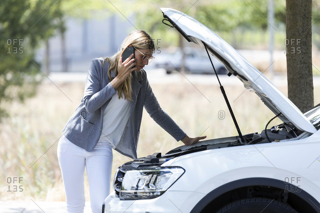Stressed young woman calling for assistance after breaking down car
