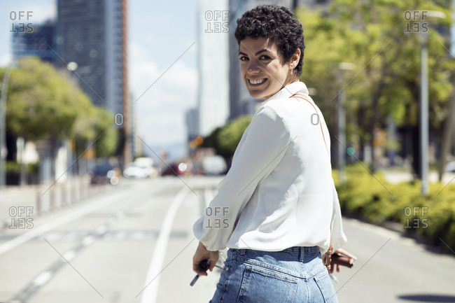 Woman looking at camera with bike on bicycle lane