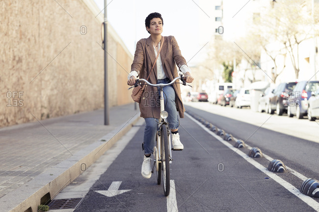 Woman with bike on bicycle lane in the city