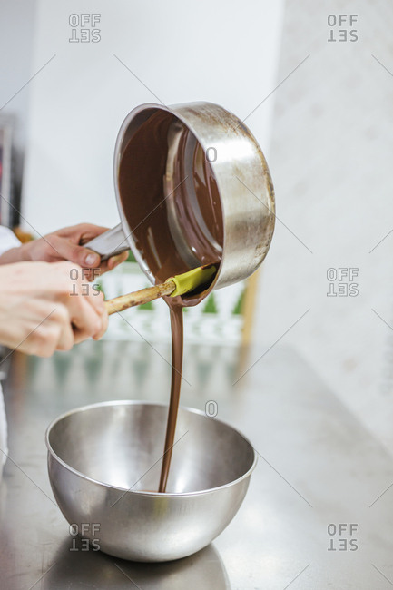 Junior chef preparing a dessert- bowl with chocolate sauce