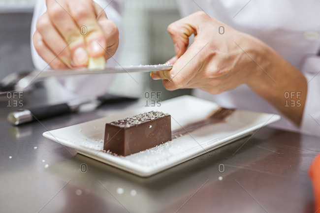 Junior chef preparing a dessert- grating coconut