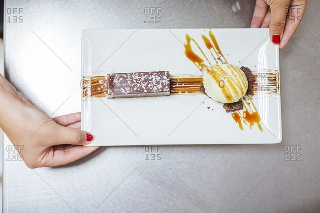 Junior chef with prepared dessert on plate- from above