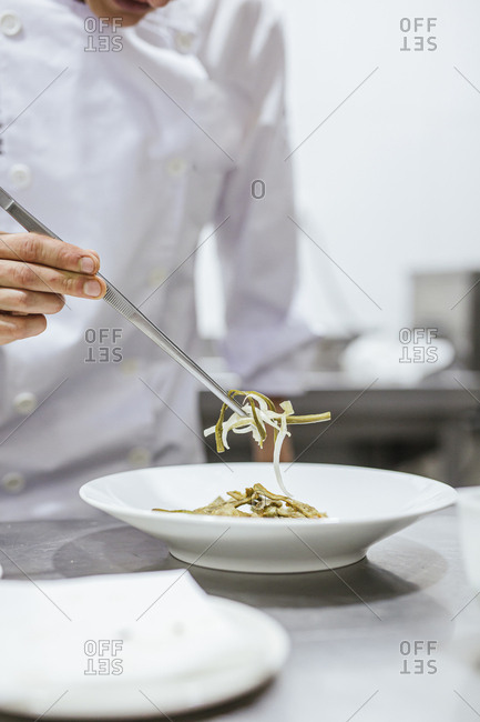 Junior chef preparing a meal on plate