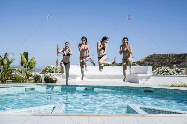 Young women enjoying the summer time at pool- jumping into the water