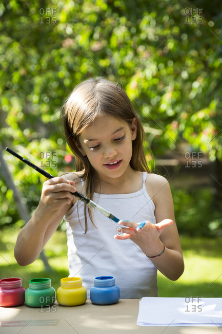 Girl in garden painting her hand with blue paint