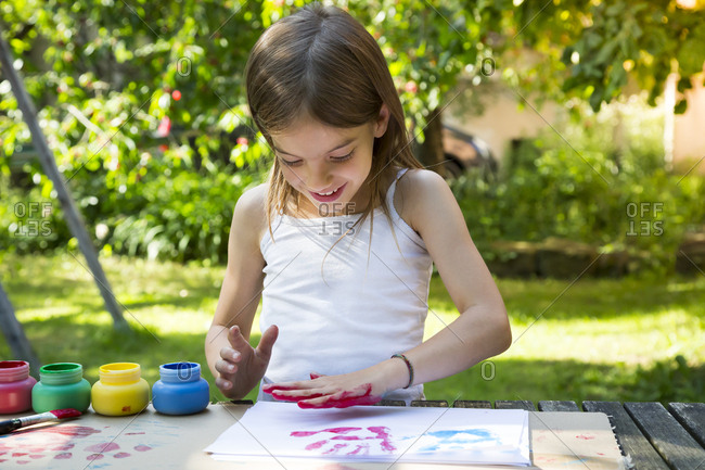 Smiling little girl printing color on sheet of paper with her hand