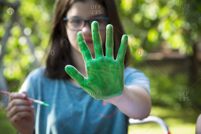 Girl's green painted hand