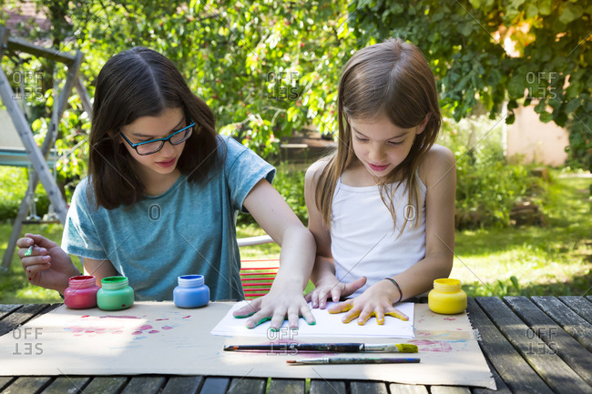 Sisters printing color on sheet of paper with their hands