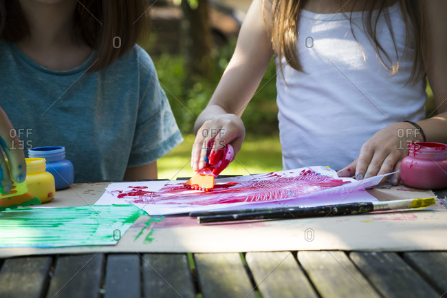 Two girls painting at table in the garden- partial view