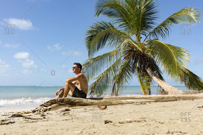 Man sitting on a tropical beach- Cahuita National Park- Costa Rica