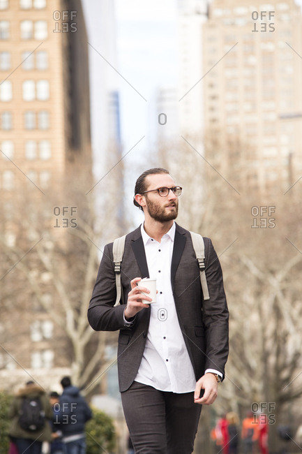 Portrait of bearded young businessman with backpack and coffee to go- New York City- USA