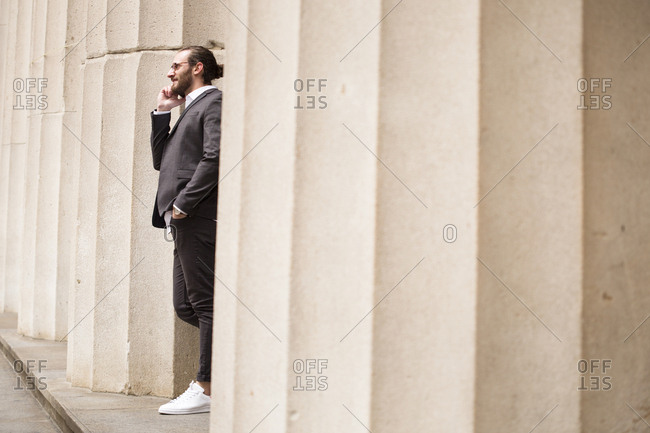 Young businessman on the phone standing among columns of Stock Exchange- New York City- USA