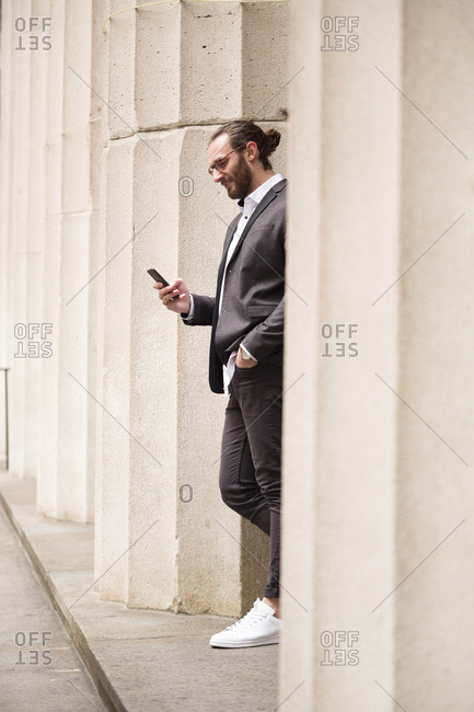 Young businessman standing among columns of Stock Exchange looking at cell phone- New York City- USA