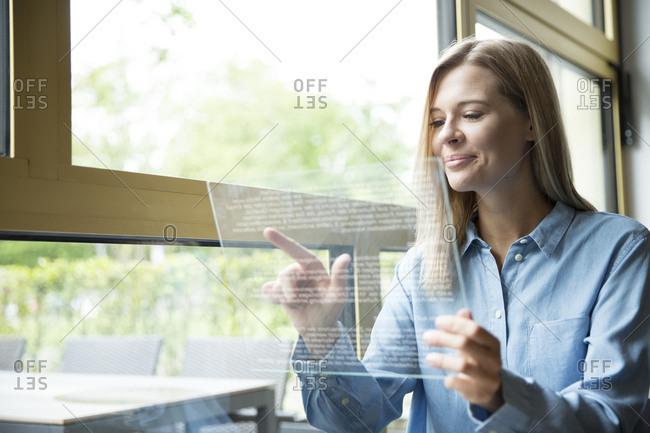 Businesswoman using futuristic tablet- glass pane