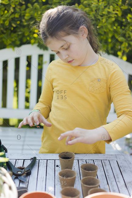Girl with nursery pots on garden table