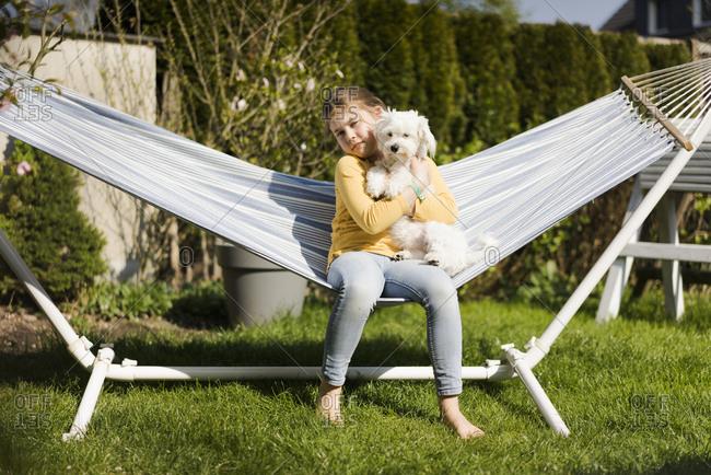 Portrait of girl with dog in hammock in garden