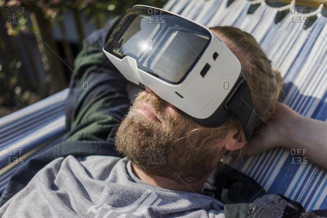 Man lying in hammock in garden wearing VR glasses