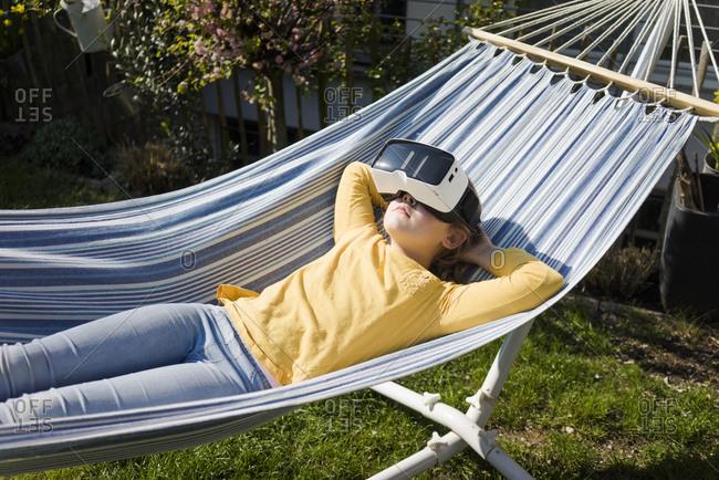 Girl lying in hammock in garden wearing VR glasses
