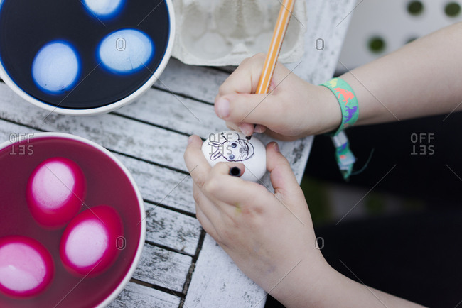 Close-up of girl painting face on Easter egg on garden table