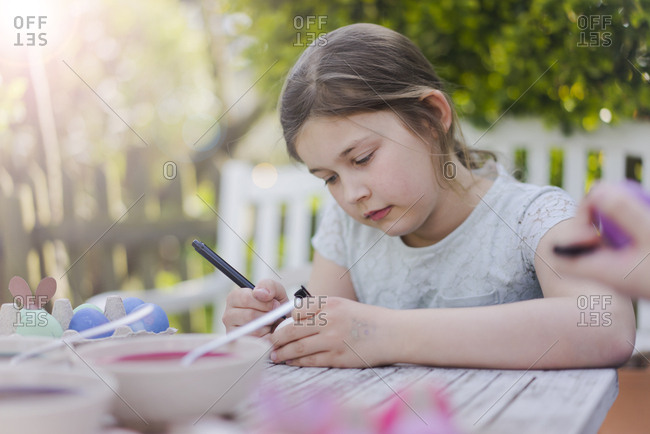 Girl painting Easter egg on garden table