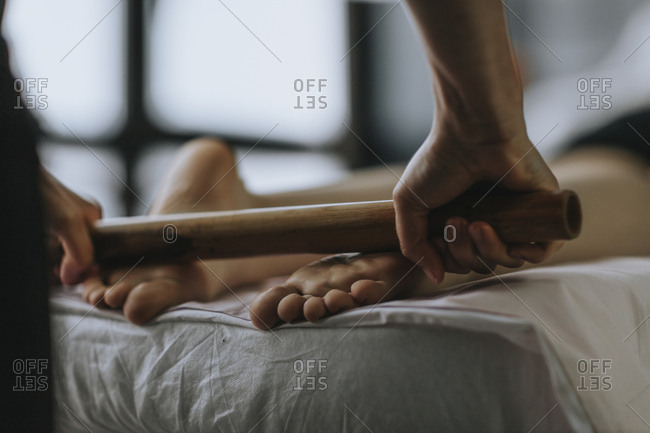 Close up of massage therapist using roller on soles of feet of female