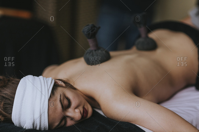 Young woman with sachets on her back during stamp massage