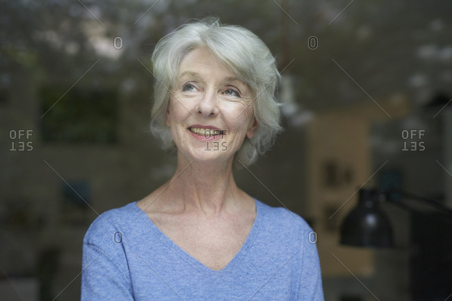 Portrait of content mature woman  looking out of window