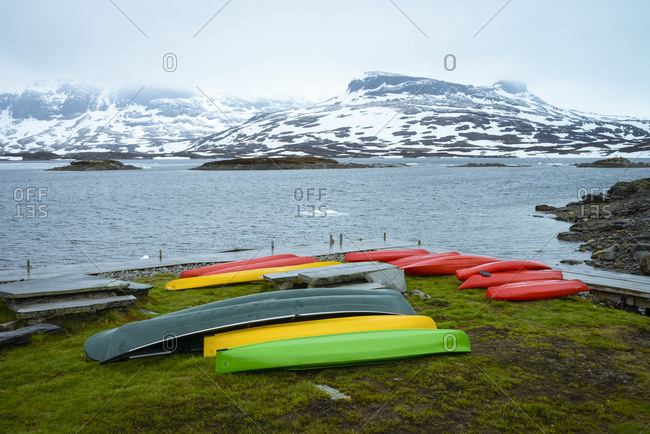 May 30, 2019: Colorful canoes at jetty- mountain range- Haukelifjell- Norway