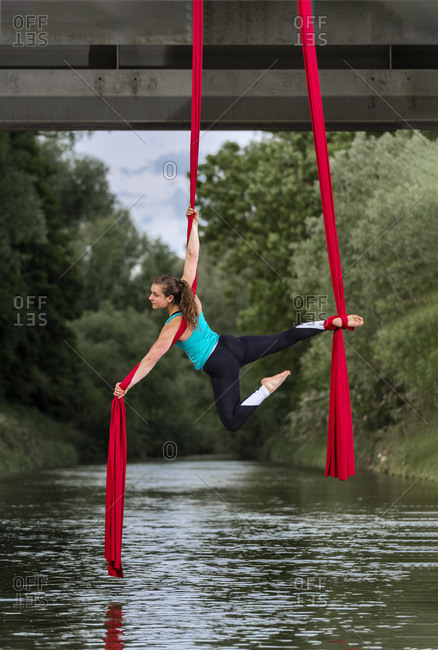Young woman doing aerial silk on a bridge