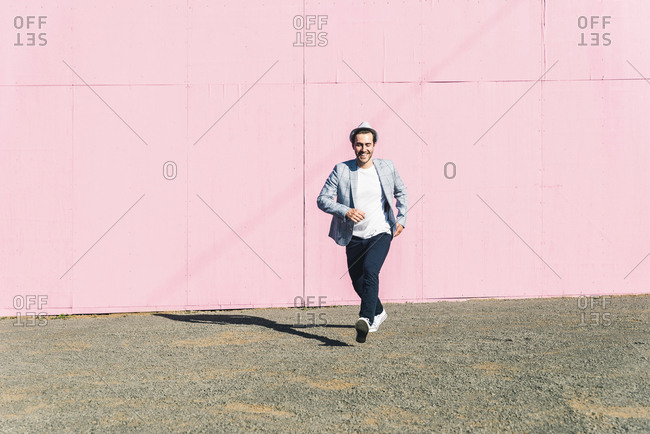 Young man in front of pink construction barrier- taking momentum