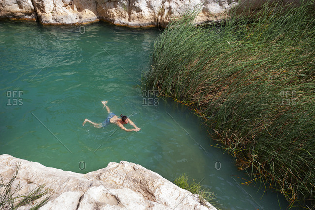 Man swimming in a small lake at Wadi Shab- Oman