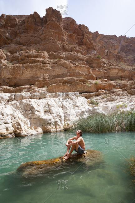 Man enjoying the sun sitting on a rock in a small lake at Wadi Shab- Oman