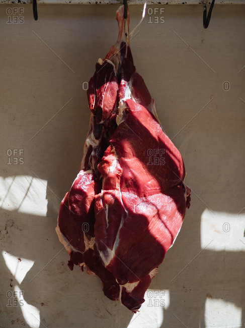 Fresh raw meat hanging on meat hook