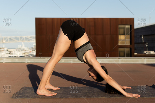 Young woman doing stretching exercises in the city of Barcelona in a sunset of summer
